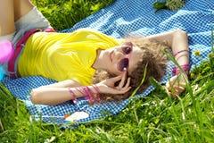Mujer joven de la felicidad en una comida campestre en el parque Imagenes de archivo