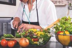 Mujer joven de la felicidad que cocina la ensalada de las verduras en la cocina Imagenes de archivo