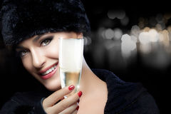 Mujer joven de la moda del invierno en sombrero de piel que tuesta con Champán Fotografía de archivo