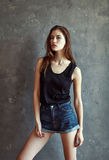 Mujer joven de la moda en fondo de la pared del grunge Foto de archivo libre de regalías