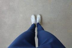 Mujer joven de la moda en tejanos y zapatillas de deporte blancas en las calles Fotografía de archivo libre de regalías