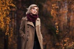 Mujer joven de la moda que camina en parque del oto?o fotografía de archivo