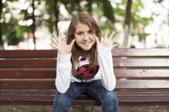 Mujer joven de la moda que sonríe en un banco Fotografía de archivo libre de regalías