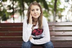 Mujer joven de la moda que sonríe en un banco Fotos de archivo