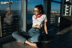 Mujer joven de la moda 90s que se sienta cerca de la ventana enorme Imagen de archivo
