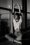 Mujer joven de la moda 90s que se sienta cerca de la ventana enorme Imagenes de archivo