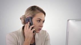 Mujer joven de la oficina que habla con alguien en su teléfono móvil en fondo de la pendiente almacen de video
