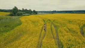 Mujer joven de la opinión del cielo que camina en un campo de flor Campo rural con las flores amarillas metrajes