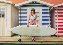 Mujer joven de la persona que practica surf con la tenencia del top y del bikini Imagenes de archivo