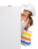 Mujer joven de la playa que mira en la cartelera en blanco Imagenes de archivo