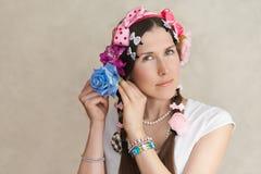 Mujer joven de la primavera que intenta en la decoración de la flor del pelo imágenes de archivo libres de regalías