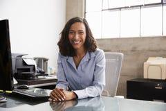 Mujer joven de la raza mixta en el escritorio de oficina que sonríe a la cámara fotografía de archivo libre de regalías