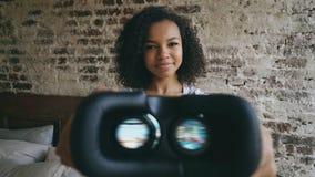 Mujer joven de la raza mixta que pone los vidrios de las auriculares del rostro humano VR 360 de realidad virtual Imágenes de archivo libres de regalías