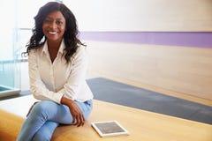 Mujer joven de la raza mixta que sienta legged cruzado, a la cámara imágenes de archivo libres de regalías