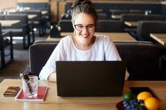 Mujer joven de la raza mixta que trabaja con el ordenador portátil en café El estudiar femenino caucásico asiático usando Interne imagen de archivo