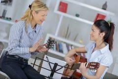 Mujer joven de la señora enseñando a cómo tocar la guitarra imágenes de archivo libres de regalías