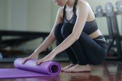 Mujer joven de la yoga que rueda su estera después de una clase de la yoga en el gimnasio cure fotografía de archivo libre de regalías