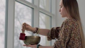 Mujer joven de la yoga que usa el cuenco del canto para relajarse metrajes