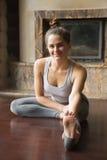 Mujer joven de la yogui en la actitud de Janu Sirsasana, backgroun del interior del hogar fotos de archivo