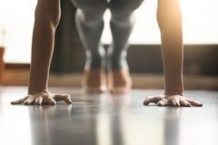 Mujer joven de la yogui que se coloca en la actitud del tablón, backgroun del interior del hogar Fotografía de archivo