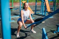 Mujer joven de los deportes atléticos que hace ejercicios en campo de deportes con los simuladores imagen de archivo