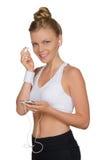 Mujer joven de los deportes con los auriculares y el teléfono Imagenes de archivo