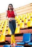 Mujer joven de los deportes en ropa de deportes en los soportes del estadio que escuchan la música en los auriculares en el teléf imagen de archivo