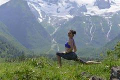 Mujer joven de los deportes que hace yoga en la hierba verde en el verano imagen de archivo