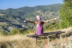 Mujer joven de los turistas en la montaña del otoño que se sienta en un banco con los brazos abiertos Imagenes de archivo