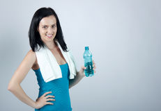 Mujer joven de Miling que sostiene una botella de agua Imágenes de archivo libres de regalías