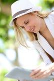Mujer joven de moda con la tableta al aire libre Foto de archivo