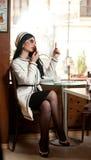 Mujer joven de moda en el equipo blanco y negro que pone el lápiz labial en sus labios y que bebe el café en restaurante Fotografía de archivo libre de regalías