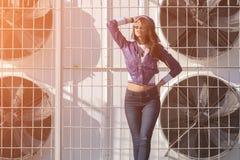 Mujer joven de moda en gafas de sol, cazadora corta de la lila y vaqueros en el fondo de acondicionadores de aire grandes ` S fa  Imágenes de archivo libres de regalías