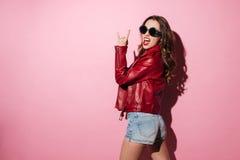 Mujer joven de moda en la chaqueta de cuero y gafas de sol Imágenes de archivo libres de regalías