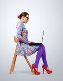 Mujer joven de moda en los vidrios que se sientan en una silla con un ordenador portátil imágenes de archivo libres de regalías