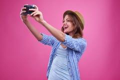 Mujer joven de moda que hace el selfie con una cámara retra de plata Imágenes de archivo libres de regalías