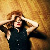 Mujer joven de moda que miente en piso de madera y que mira para arriba Foto de archivo libre de regalías