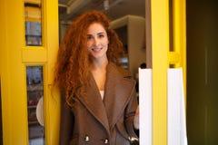 Mujer joven de moda que sale fuera de una cafetería imagen de archivo libre de regalías