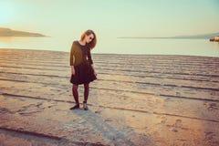 Mujer joven de moda que se coloca en la playa en la puesta del sol Foto de archivo