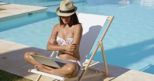 Mujer joven de moda que se relaja en la piscina metrajes