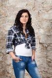 Mujer joven de pelo largo en la pared de piedra vieja Fotos de archivo
