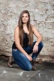 Mujer joven de pelo largo en la pared de piedra vieja Imagenes de archivo
