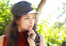 Mujer joven de pensamiento atractiva en el casquillo que sostiene los vidrios de sol Fotos de archivo