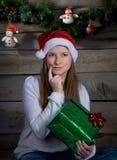 Mujer joven de pensamiento en Santa Hat With Christmas Gift. Año Nuevo. imagenes de archivo