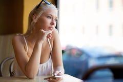 Mujer joven de pensamiento que mira hacia fuera la ventana Imágenes de archivo libres de regalías