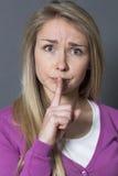Mujer joven de pensamiento que quiere mantener cosas reservadas y confidenciales Fotografía de archivo libre de regalías