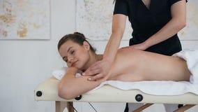 Mujer joven de relajaci?n que tiene masaje en la parte posterior en sal?n del balneario almacen de video