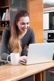 Mujer joven de risa con el ordenador a trabajar a distancia o a comprar en línea Fotografía de archivo libre de regalías