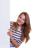 Mujer joven de risa con el pelo rubio detrás de un letrero Fotos de archivo