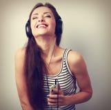 Mujer joven de risa en auriculares que escucha el reproductor Mp3 Fotos de archivo